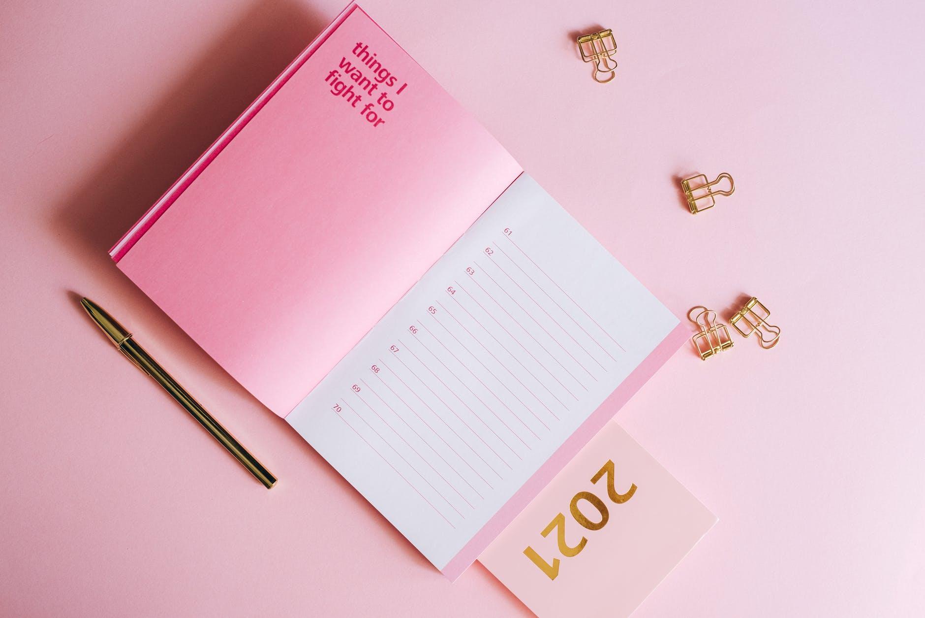 white notebook beside silver pen